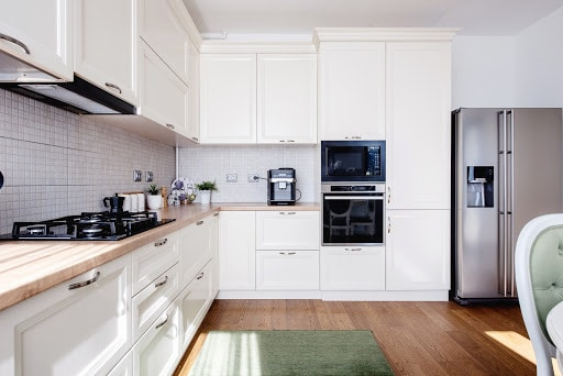 Modern kitchen interior with hardwood floors and wooden white creamy furniture